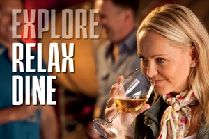 A lady with long blonde hair and a floral scarf around her neck sniffs a white wine at a wine tasting session in the Granite Belt. www.wellcamp.com.au